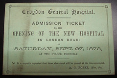 "A rectangular green cardboard ticket reading: ""Croydon General Hospital.  Admission ticket to the opening of the new hospital in London Road: on Saturday, Sept. 27, 1873, at two o'clock precisely.  It is urgently requested that those who attend will be present at the time appointed.  A. G. Roper, Hon. Sec."""