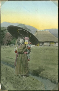 Japanese girl with an umbrella and a child in a baby carrier