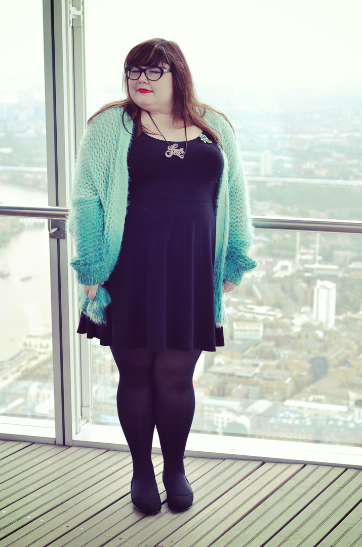 Image: me in my black dress, mint cardigan and glasses overlooking part of the London skyline.
