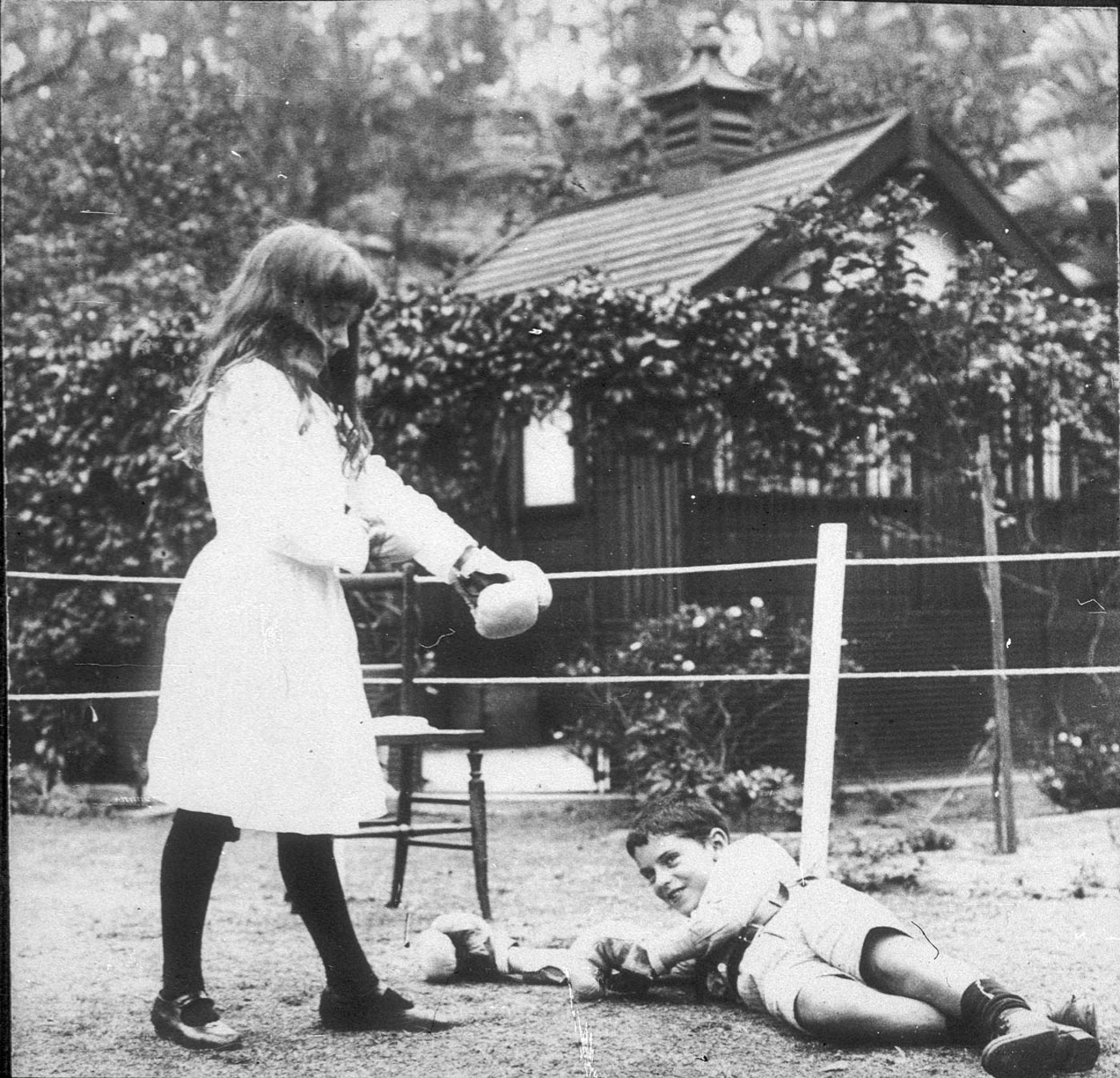 Banjo Paterson's children Grace and Hugh boxing with Christmas present gloves, Sydney, NSW, 1919 / photographer unknown