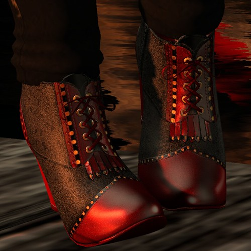 Image Description: Close up of a pair of ankle boots with red lacings.
