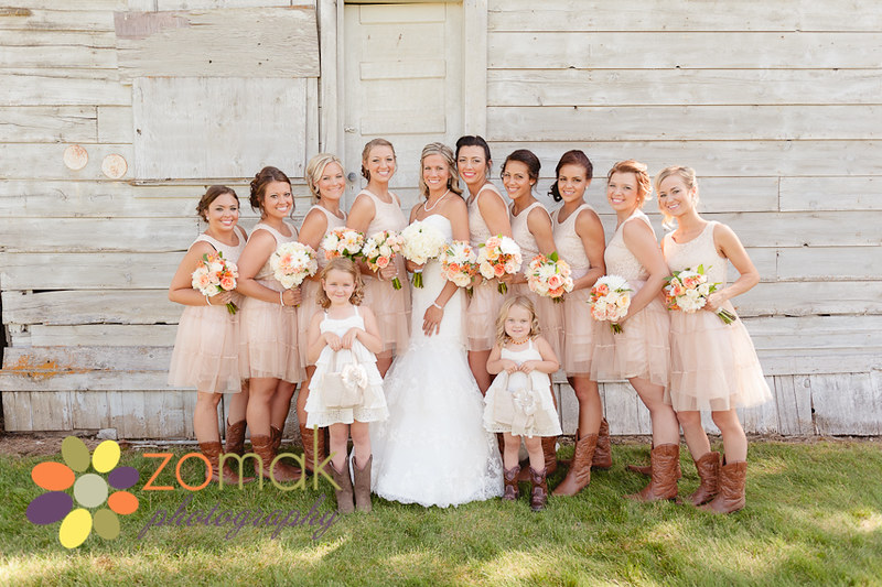 Sweet shot of the bridesmaids, bride and flower girls near a barn on the farm property.