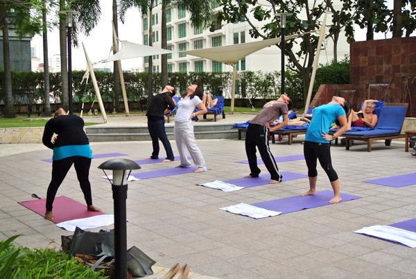 Guests having a calming yoga session by the poolside