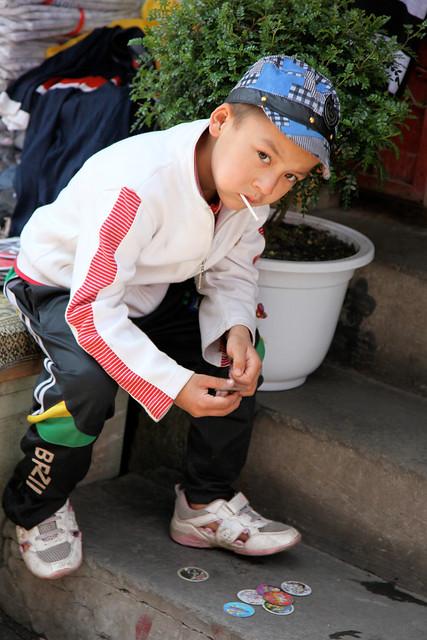 A boy playing with pogs, Urumqi ウルムチ、メンコで遊ぶ少年