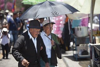 No chance of rain - old man and woman sheltering from the sun at La Fiesta de la Virgen de la Merced
