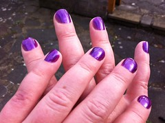 A white person's hands crossed on top of each other. Their nails are short and rounded and have been painted purple. Grey crazing paving is visible in the background.