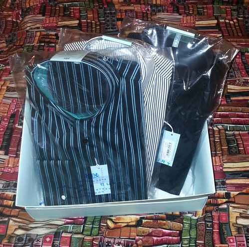 New shirts in box on bed