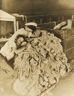 Boys sleeping on idle fishing nets in Riviera Beach, Florida