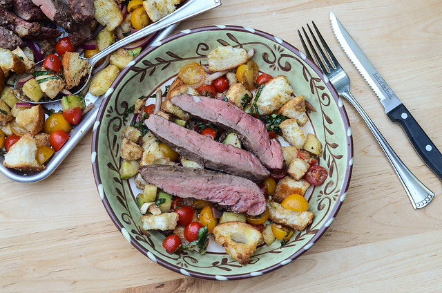Grilled steak on top of bread salad in a bowl.