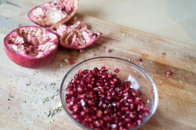 the easy way to deseed a pomegranate - just pull apart, turn over a bowl and bang with a wooden spoon