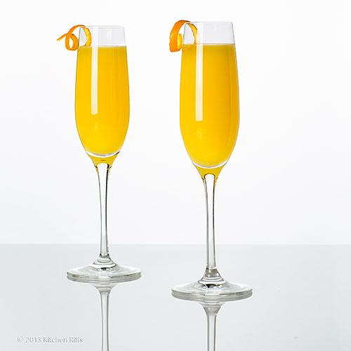 Mimosa Cocktails with orange twist garnish, on white acrylic