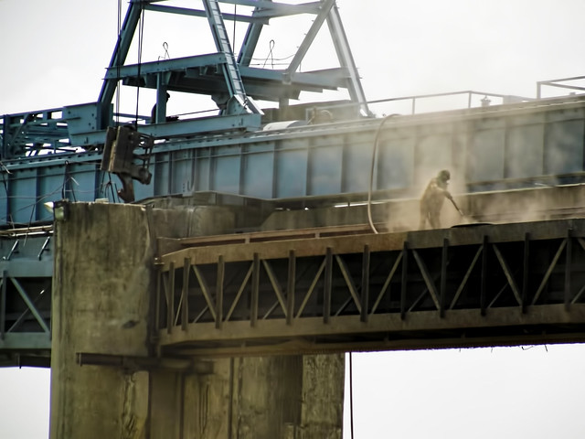 A worker cleaning fly-ash dust on the Hasdeo barrage in Korba. Fly-ash causes air pollution and affects the health of the residents near the plants.