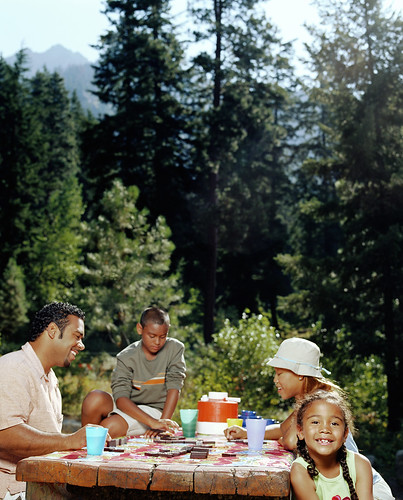 Father and mother sitting with son and daughter at picnic table. Photo courtesy of ThinkStock.
