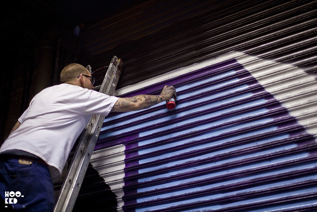 Street Artist Ben Eine at work spray painting a roller shutter