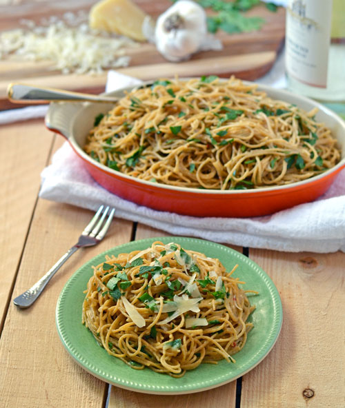 Garlic pasta in a red baking dish and served on a green plate