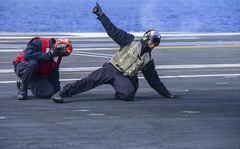 Aviation Machinist's Mate 3rd Class Andre Payne signals all clear for the launch of an F/A-18E Super Hornet aboard aircraft carrier USS Carl Vinson (CVN 70), Feb. 8. (U.S. Navy/MC2 John Philip Wagner)