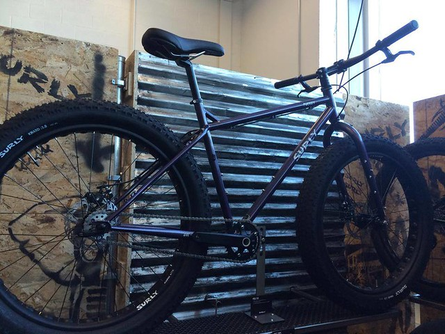 Right side view of a Surly Pugsley SS fat bike, leaning on a short steel wall, inside of a warehouse