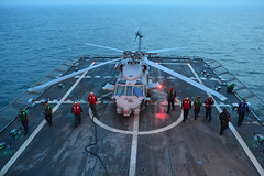 Sailors aboard USS Freedom (LCS 1) clear the flight deck of debris prior to launching an MH-60R helicopter off the coast of Malaysia for an amphibious assault exercise rehearsal, June 21. (U.S. Navy photo by Mass Communication Specialist 1st Class Cassandra Thompson)