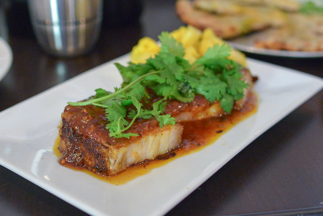 Mango Jam Glazed Pork Belly rubbed in aromatic spices and pan-seared with spiced mango jam, topped with cilantro