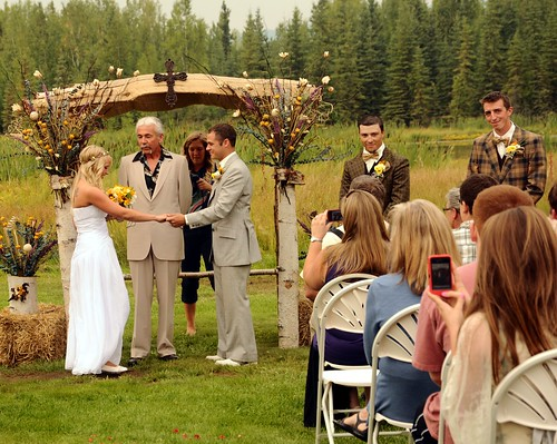 Jessie about to marry her beau, Chris, officiant, groomsmen in vintage clothing, photographer, audience with camera phones, country style, cross topping the white birch wedding arch, Fairbanks, Alaska, USA by Wonderlane