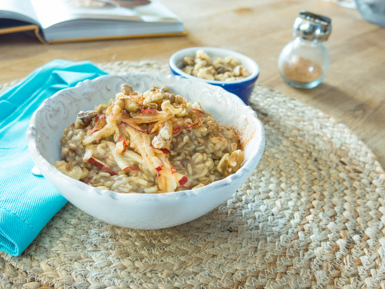 cooked whole oat groats with apples and cinnamon in a white bowl