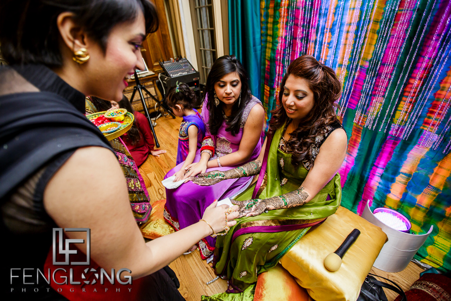 Indian bride greeting guests with henna on hands