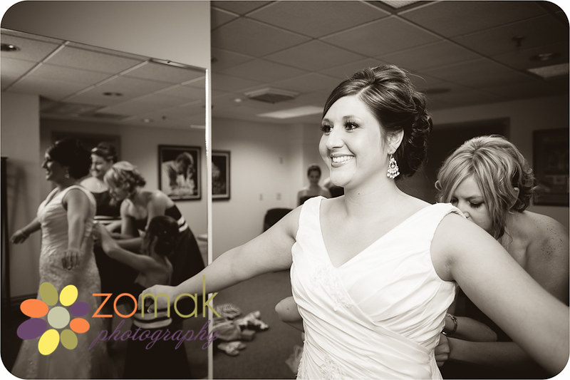 Best getting ready photo of bride with bridesmaids putting on her gown.