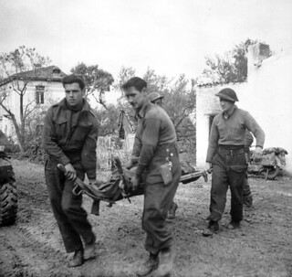 Infantrymen of The Seaforth Highlanders of Canada carrying a comrade who was killed... / Des soldats d'infanterie des Seaforth Highlanders of Canada transportent un camarade tué...