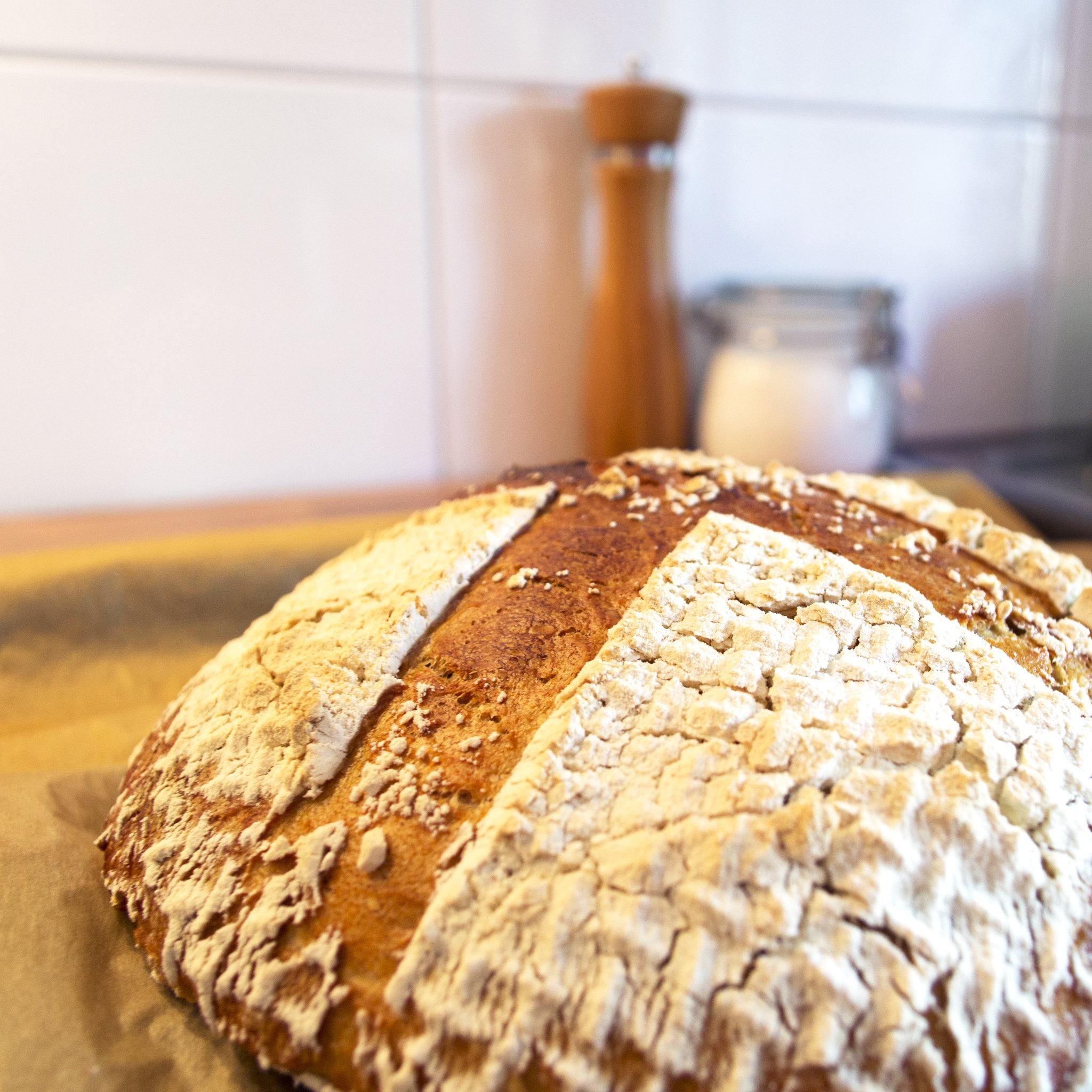 Wenn ich Brot baue, dann kommt so etwas dabei heraus. (Bildbeschreibung: Im Vordergrund liegt ein Brotlaib, mittelbraun, mehrheitlich mit Mehl bedeckt, nur zwei breite Streifen sind frei. Dahinter stehen, unscharf nur noch zu erkennen, eine hölzerne Pfeffermühle und ein Einweckglas voller Salz vor einem weißen Fliesenspiegel.)