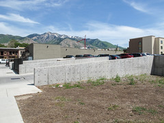 High and holey concrete walls for a parking lot driveway, with Wasatch Mountains.