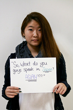 "A woman stands with a sign ""So what do you guys speak in Japan, Asian?"""