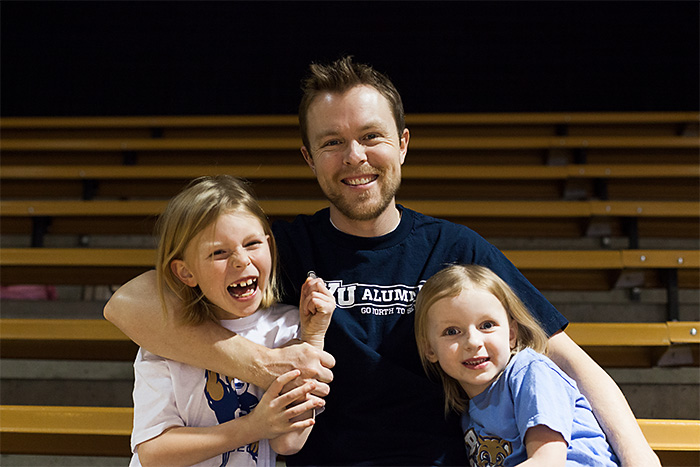 Bart Francis with his two daughters, Addison and Hannah in the bleachers of a BYU Basketball game