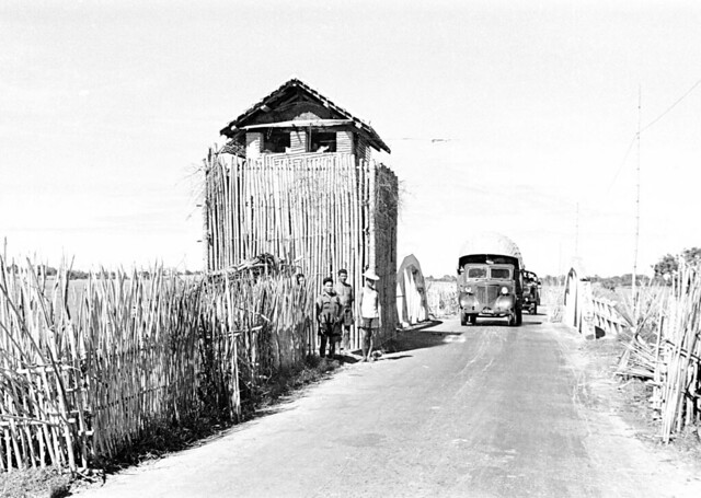 1950 Trucks passing watchtower in Tây Ninh