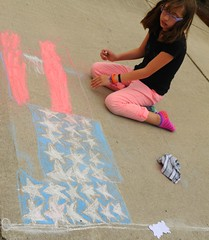 Ellie creating an American flag 3-d design on the 4th of July, colored chalk on concrete, eraser rag, West Olympia, Washington, USA