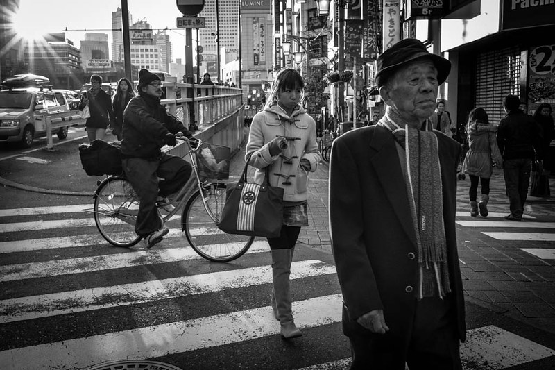 A cyclist, a woman and an old man at the zebra crossing at Shinjuku
