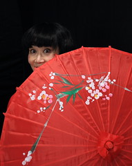 geisha(0.0), clothing(0.0), costume(0.0), pink(0.0), umbrella(1.0), red(1.0), woman(1.0),