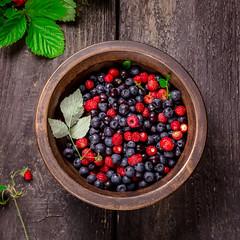 Bowl with wild berries on dark wooden background.
