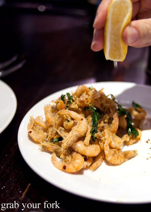 Squeezing lemon onto fried school prawns at Fix St James, Sydney