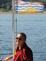 Dilgo Khyentse Yangsi Rinpoche, on board a ship, wearing sunglasses, being photographed (by many photographers out of the frame),  semchen tsetar tangpa, British Columbia, Canada