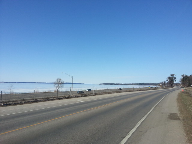 Highway next to body of water, peninsula in the distance