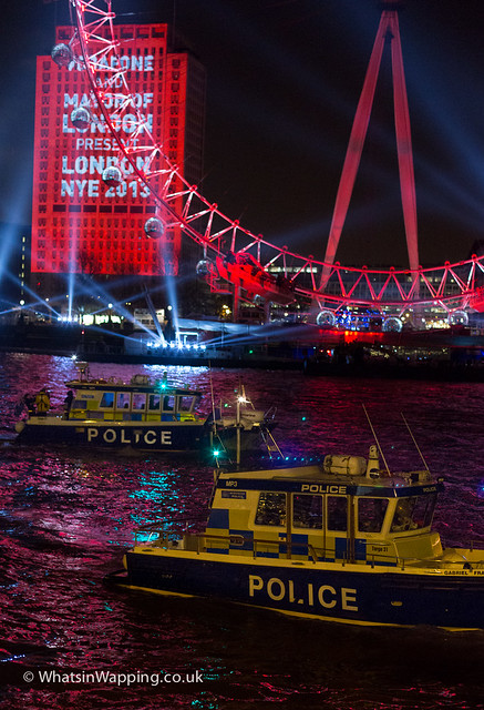 Marine Police Unit boats pass the London Eye on New Year's Eve