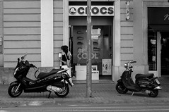 motorcycle(0.0), scooter(1.0), vehicle(1.0), mode of transport(1.0), road(1.0), monochrome photography(1.0), monochrome(1.0), black-and-white(1.0), street(1.0), black(1.0), infrastructure(1.0), vespa(1.0),