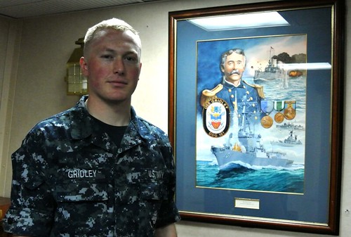 Culinary Specialist Seaman James P. Gridley stands next to poster of Capt. Charles Vernon Gridley, his great, great grandfather.