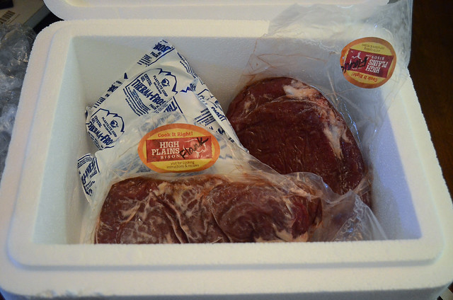 A disposable cooler filled with frozen bison flank steaks.
