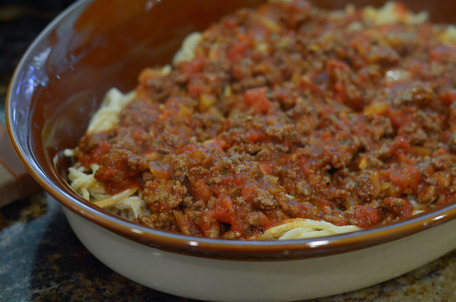 The spaghetti and meat sauce are layered in a casserole dish.