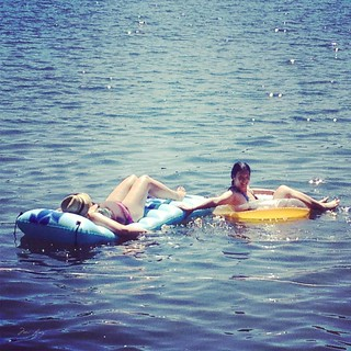 Kristen and Mei floating on the lake on their floatation devices