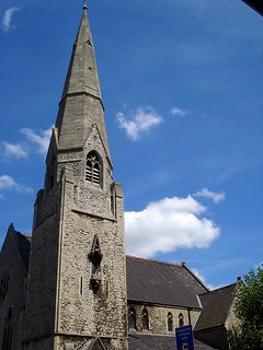 A grey stone church with a slate roof and a tower topped with a spire.