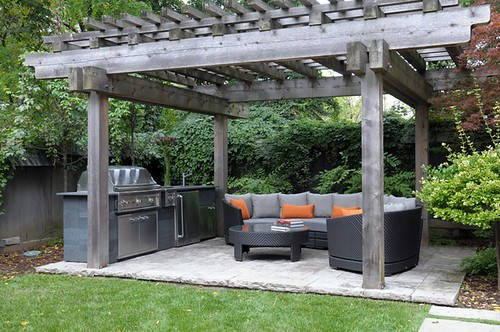 sectional patio set in garden with pergola
