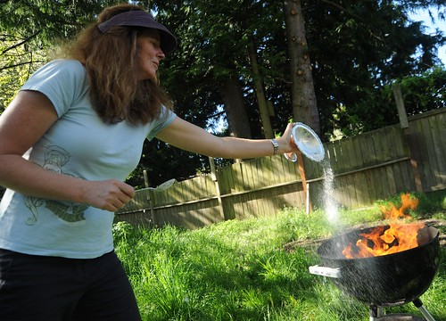 The last of the Sur, Charlotte offering the last bit of white food, silver compote, fire in a barbeque, backyard, grass, fence, Seattle, Washington, USA by Wonderlane