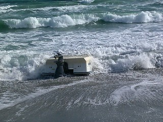 A capsized 21-foot center console vessel washes ashore in the vicinity of St. Lucie Inlet, Fla., Nov. 22, 2013. Jupiter Police Department reported the capsized vessel to Coast Guard watchstanders. The Coast Guard is searching for suspected migrants in the water. U.S. Coast Guard photo